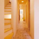 1F廊下部分。暖色照明やタイル状の床。やや狭さを圧迫感を感じさせるのは2Fに上がった時の驚きと感動を倍増させるための演出なのかもしれません。