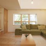 2F部分のリビング。大人数の来客でも対応できる大容量ソファ。日々の暮らしを落ち着いたものにする木調の床が特徴