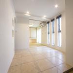 玄関ホール。右には3連の細窓で明るいつくり。左の部屋に行く仕切りの上部が円弧状になっていておしゃれです。