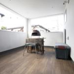 インナーバルコニー。床が木調で、ここ椅子テーブル出したり、あるいはゴザ敷いて過ごすのも心地好さそうです。写真はバーベキューセット。庭がなくても、こういう形でも1つの日本人の夢、「家庭でバーベキュー」を実現できるのですね。